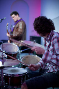 man facing away from camera drumming during a gig in 2010